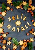 FELIZ NATAL-KOEKJES Woorden Vrolijke Kerstmis het Engelse Portugees met gebakken koekjes, Kerstmisdecoratie en noten op zwarte Stock Afbeelding