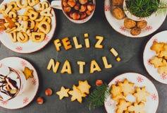 FELIZ NATAL-KOEKJES Woorden Vrolijke Kerstmis het Engelse Portugees met gebakken koekjes, Kerstmisdecoratie en noten op zwarte Royalty-vrije Stock Afbeelding