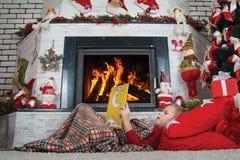 Feliz Natal! Menino bonito que lê um livro que encontra-se no tapete perto da chaminé imagem de stock