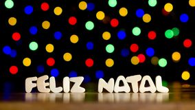Feliz natal, merry christmas in Portuguese language. Text, beautiful multicolor bokeh background with copy space Royalty Free Stock Photo