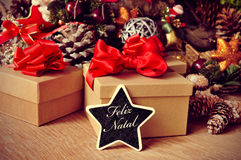 Feliz natal, merry christmas in portuguese. A star-shaped chalkboard with the text feliz natal, merry christmas in portuguese, on a rustic wooden table full of Stock Photo