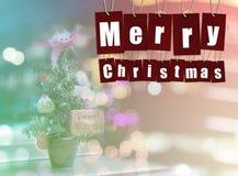 Feliz Natal a palavra do alfabeto em etiquetas de papel vermelhas no bokeh ilumina-se Fotos de Stock Royalty Free