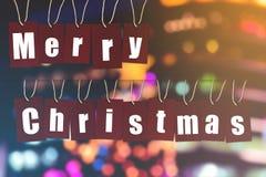 Feliz Natal a palavra do alfabeto em etiquetas de papel vermelhas no bokeh ilumina-se Fotografia de Stock Royalty Free