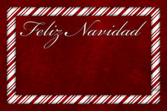 Feliz Navidad. A Feliz Navidad card, A Candy Cane border with words Feliz Navidad over red plush background with copy-space Royalty Free Stock Photography
