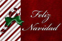 Feliz Navidad. A Feliz Navidad card, A Candy Cane with words Feliz Navidad over red plush background stock photo