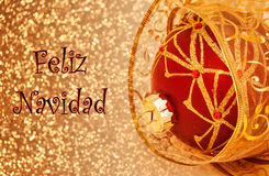 Feliz Navidad Card. A Feliz Navidad card, with text, red ornament and gold ribbon Royalty Free Stock Photo