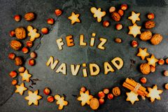 FELIZ NAVIDAD COOKIES. Words Merry Christmas en Spanish with baked cookies, Christmas decoration and nuts on black slate. Background. Christmas card for stock photos