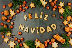 FELIZ NAVIDAD COOKIES. Words Merry Christmas en Spanish with baked cookies, Christmas decoration and nuts on black slate. Background. Christmas card for stock photography