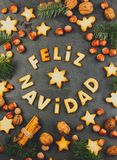 FELIZ NAVIDAD COOKIES. Words Merry Christmas en Spanish with baked cookies, Christmas decoration and nuts on black slate. Background. Christmas card for Stock Image