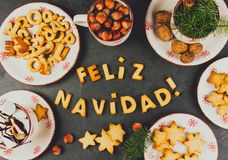 FELIZ NAVIDAD COOKIES. Words Merry Christmas en Spanish with baked cookies, Christmas decoration and nuts on black slate. Background. Christmas card for royalty free stock images