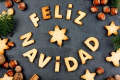 FELIZ NAVIDAD COOKIES. Words Merry Christmas en Spanish with baked cookies, Christmas decoration and nuts on black slate. Background. Christmas card for royalty free stock photo