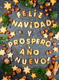 FELIZ NAVIDAD COOKIES. Words text Merry Christmas and Happy New Year en Spanish with baked cookies, Christmas decoration. And nuts on black slate background Stock Images