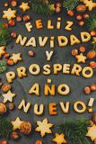 FELIZ NAVIDAD COOKIES. Words text Merry Christmas and Happy New Year en Spanish with baked cookies, Christmas decoration. And nuts on black slate background Royalty Free Stock Photos