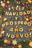 FELIZ NAVIDAD COOKIES. Words text Merry Christmas and Happy New Year en Spanish with baked cookies, Christmas decoration. And nuts on black slate background Royalty Free Stock Image