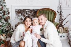 Feliz Navidad de la familia cariñosa y Feliz Año Nuevo Gente bonita alegre Mamá y papá que abrazan a la pequeña hija padres foto de archivo