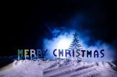 Feliz Navidad de las palabras en un campo de nieve, con el fondo oscuro con el árbol de los chrismas Concepto del Año Nuevo Espac foto de archivo libre de regalías