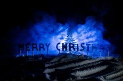 Feliz Navidad de las palabras en un campo de nieve, con el fondo oscuro con el árbol de los chrismas Concepto del Año Nuevo Espac fotografía de archivo