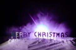 Feliz Navidad de las palabras en un campo de nieve, con el fondo oscuro con el árbol de los chrismas Concepto del Año Nuevo Espac fotos de archivo