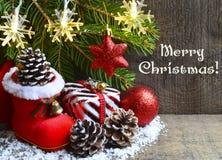 Feliz Navidad Decoración de la Navidad: bota del ` s de Papá Noel, árbol de abeto, caja de regalo, conos del pino y juguetes rojo Imagen de archivo libre de regalías