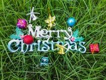 Feliz Navidad decorativa en hierba verde Fotos de archivo libres de regalías