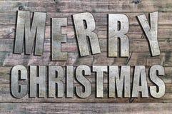 Feliz Navidad del hierro escrita en el tablero de madera Fotografía de archivo libre de regalías