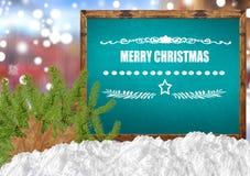 Feliz Navidad en la pizarra azul con el pino y la nieve de la ciudad del blurr Fotografía de archivo