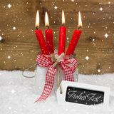 Feliz Navidad en lengua alemana con cuatro velas rojas Fotos de archivo libres de regalías