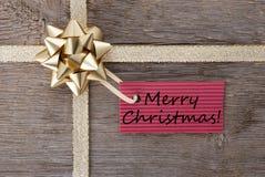 Feliz Navidad en una etiqueta roja Foto de archivo