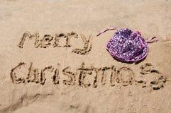 Feliz Navidad escrita en la arena Imágenes de archivo libres de regalías