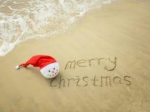 Feliz Navidad escrita en la arena blanca de la playa tropical con el muñeco de nieve Foto de archivo