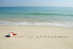 Feliz Navidad escrita en la arena tropical del blanco de la playa Imagenes de archivo