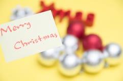 Feliz Navidad escrita en la hoja amarilla: decoraciones b de la Navidad imagenes de archivo