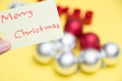 Feliz Navidad escrita en la hoja amarilla: decoraciones b de la Navidad foto de archivo