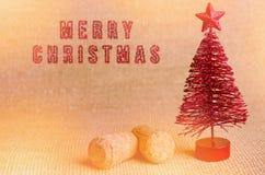 Feliz Navidad escrita por el cepillo rojo brillante Árbol de navidad artificial rojo con el corcho del champán en fondo brillante Foto de archivo libre de regalías
