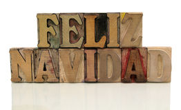 Feliz navidad in letterpress wood type. The words 'feliz navidad' in old wood type isolated on white with a reflection royalty free stock photo