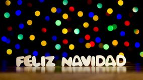 Feliz navidad, merry christmas in Spanish language. Text, beautiful multicolor bokeh background with copy space stock photos