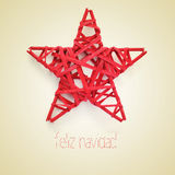 Feliz navidad, merry christmas in spanish. A red christmas star and the sentence feliz navidad, merry christmas written in spanish, on a beige background, with a royalty free stock photo