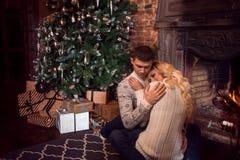 Feliz Navidad Pares jovenes que celebran Año Nuevo en casa Abrazo del hombre y de la mujer Imagen de archivo libre de regalías