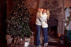 Feliz Navidad Pares jovenes que celebran Año Nuevo en casa Abrazo del hombre y de la mujer Imagen de archivo