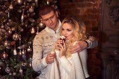 Feliz Navidad Pares jovenes que celebran Año Nuevo en casa Cacao de consumición del hombre y de la mujer Fotos de archivo