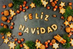 FELIZ NAVIDAD-PLÄTZCHEN En-Spanisch der Wort-frohen Weihnachten mit gebackenen Plätzchen, Weihnachtsdekoration und Nüssen auf sch stockfotografie