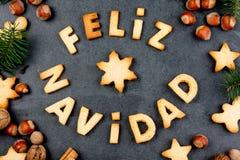 FELIZ NAVIDAD-PLÄTZCHEN En-Spanisch der Wort-frohen Weihnachten mit gebackenen Plätzchen, Weihnachtsdekoration und Nüssen auf sch lizenzfreies stockfoto