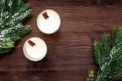 Feliz Navidad por la tarde del invierno con la bebida del alcohol Yema con canela y picea en la opinión superior del fondo de mad foto de archivo