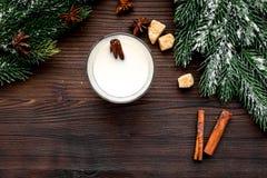 Feliz Navidad por la tarde del invierno con la bebida del alcohol Yema con canela y picea en la opinión superior del fondo de mad foto de archivo libre de regalías