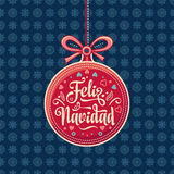 Feliz Navidad.  Red Christmas ball with good wishes in Spanish. Royalty Free Stock Photo