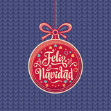 Feliz Navidad.  Red Christmas ball with good wishes in Spanish. Royalty Free Stock Image