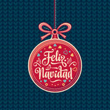 Feliz Navidad.  Red Christmas ball with good wishes in Spanish. Stock Photos
