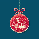 Feliz Navidad.  Red Christmas ball with good wishes in Spanish. Colorful greeting card Royalty Free Stock Photo