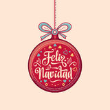 Feliz Navidad.  Red Christmas ball with good wishes in Spanish. Colorful greeting card Stock Image