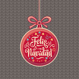 Feliz Navidad.  Red Christmas ball with good wishes in Spanish. Colorful greeting card Stock Images